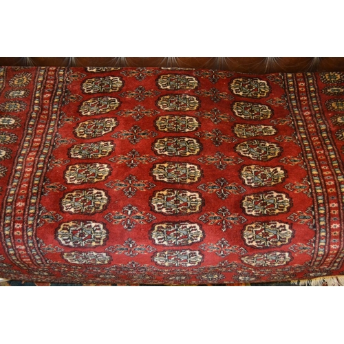 12 - Pakistan rug of Turkoman design with three rows of gols on a wine ground...