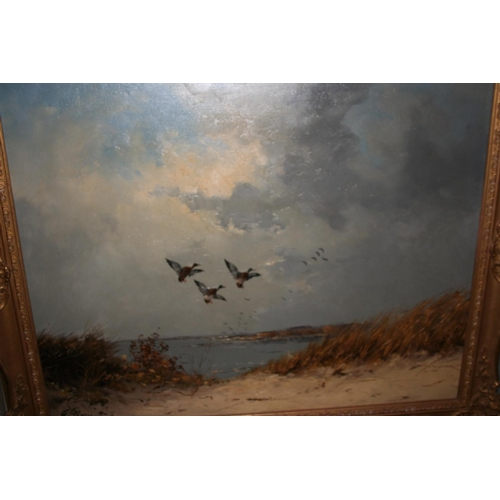 1342 - G. Stevens, oil on canvas, mallards in flight above a lake, 24ins x 36ins, in a swept gilt frame...