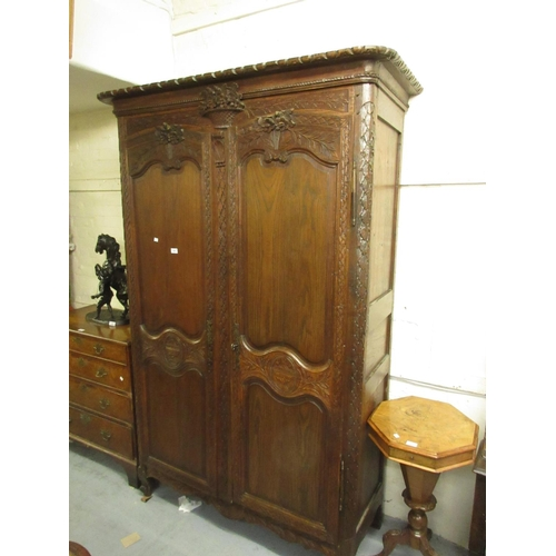 1894 - 19th Century French carved oak armoire with a moulded cornice above two doors raised on low scroll s...