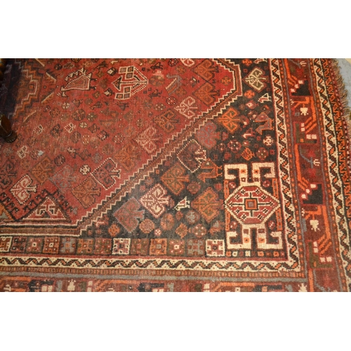 6 - Shiraz carpet of medallion design on a red and black ground with borders, 6.5ft x 9.5ft approximatel...
