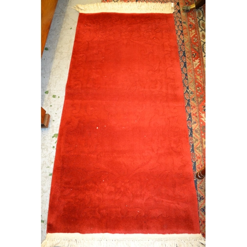 9 - Three various small Chinese red ground rugs...