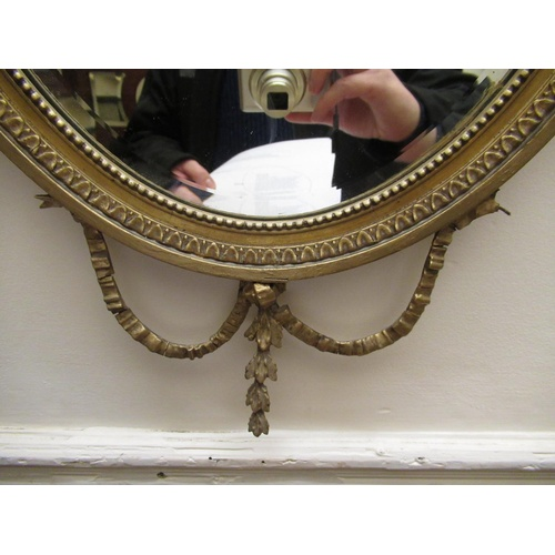 1901 - Small oval gilt framed bevelled edge wall mirror with urn and swag surmount...