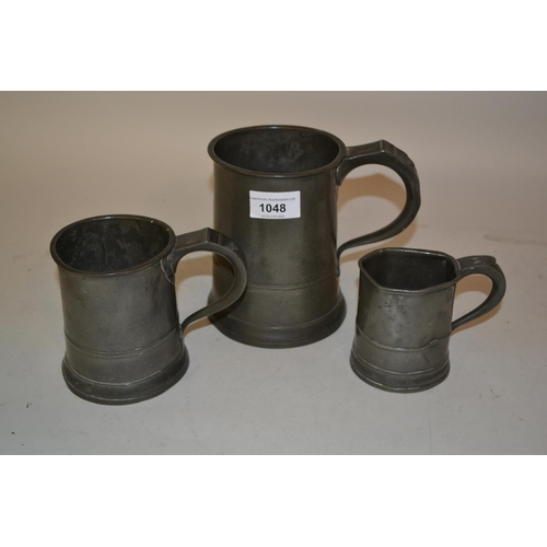 1048 - Antique pewter quart mug, together with a matching one pint mug and matching half pint mug (at fault...