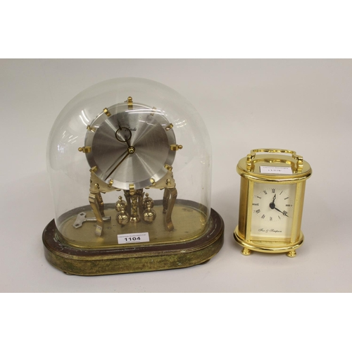 1104 - Kundo brass Anniversary clock under a glass dome, together with a modern brass cased carriage clock...