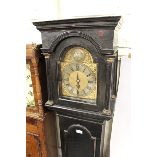 1127 - 18th Century ebonised longcase clock, the broken arch hood above a moulded panel door and conforming...
