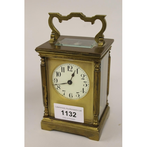 1132 - Gilt brass carriage clock, the circular dial with Arabic numerals, housed in original leather travel...
