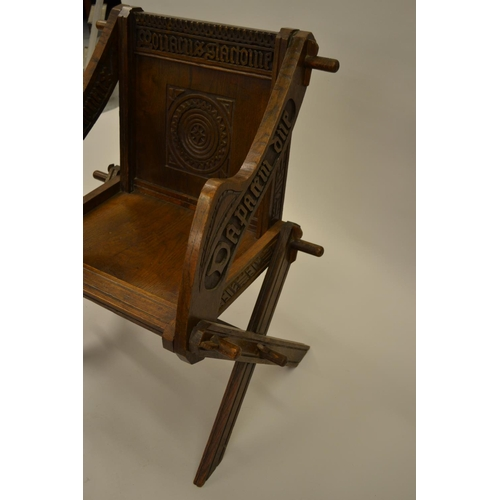 1588 - Late 19th Century oak Glastonbury type chair with carved panel back and arms, raised on crossover su...