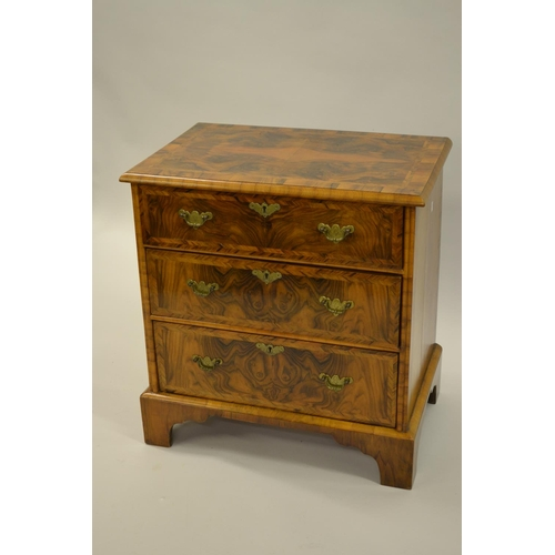 1618 - Small reproduction figured walnut and crossbanded three drawer chest raised on bracket feet...