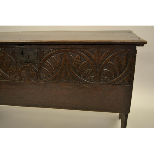 1628 - 17th Century oak plank coffer, the hinged chip carved lid above a carved frieze and chip carved fron...