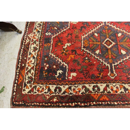 4 - 20th Century Shiraz rug with a pole medallion design on red ground, 5ft 6ins x 4ft 2ins approximatel...