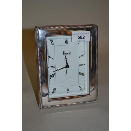 582 - Modern silver mounted battery clock, the dial inscribed Harrods...