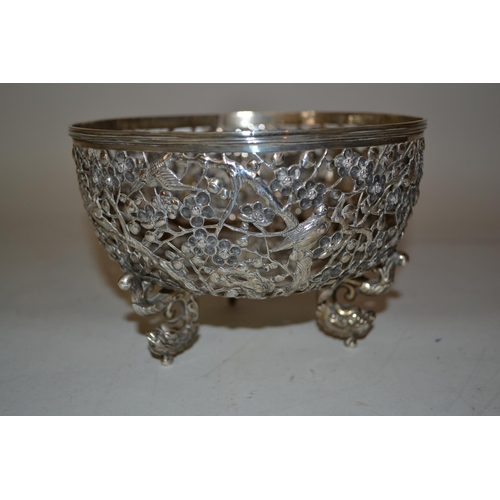 588 - Chinese silver bowl of circular pierced design, decorated in relief with prunus blossom and exotic b...