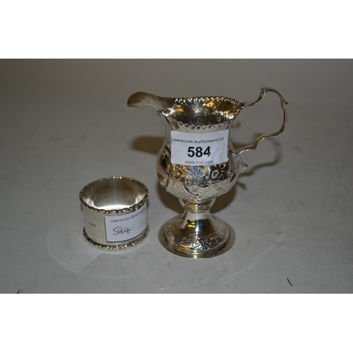 584 - George III floral embossed silver cream jug together with a silver napkin ring...