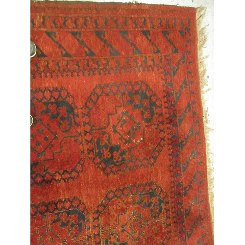 6 - Afghan carpet with typical gol design on a red ground, 10ft x 7ft 6ins approximately...