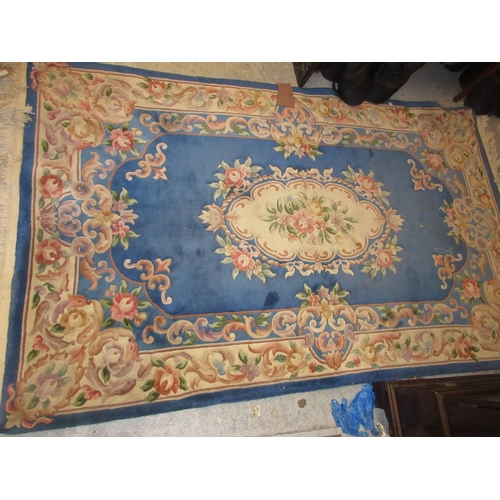 9 - Chinese rug with typical embossed floral design on a blue ground...