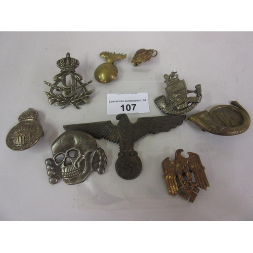 107 - Bag containing a small collection of various military badges including Luftwaffe, skull and cross bo...