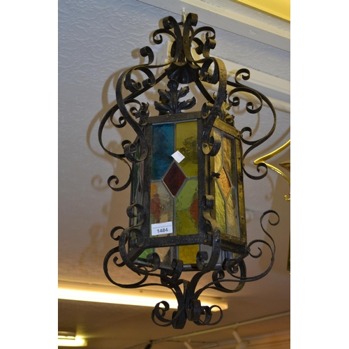 1484 - Early 20th Century wrought iron and coloured leaded glass hexagonal hall lantern, 27ins high...