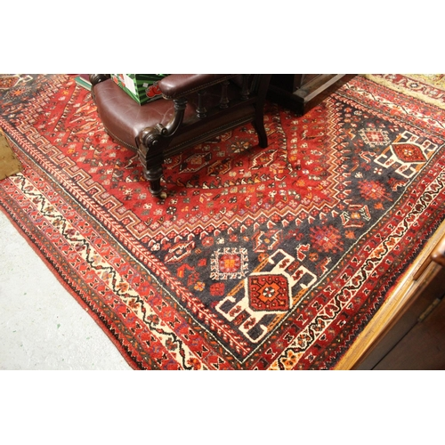 15 - Shiraz carpet of centre medallion and all-over geometric design with borders on a wine ground, appro...
