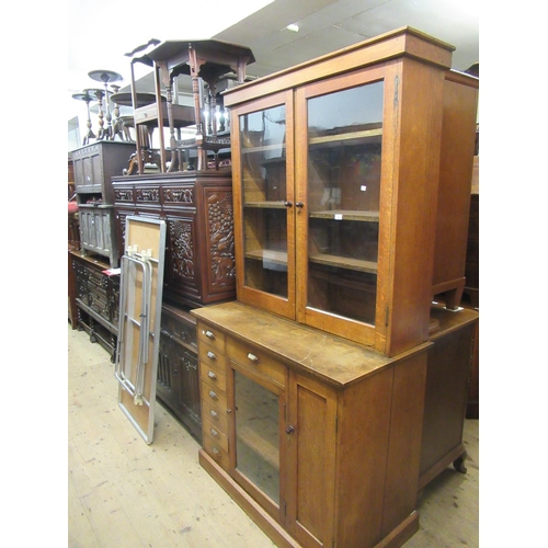 2107 - Early 20th Century oak estate cupboard with a pair of glazed doors, the base with an arrangement of ...