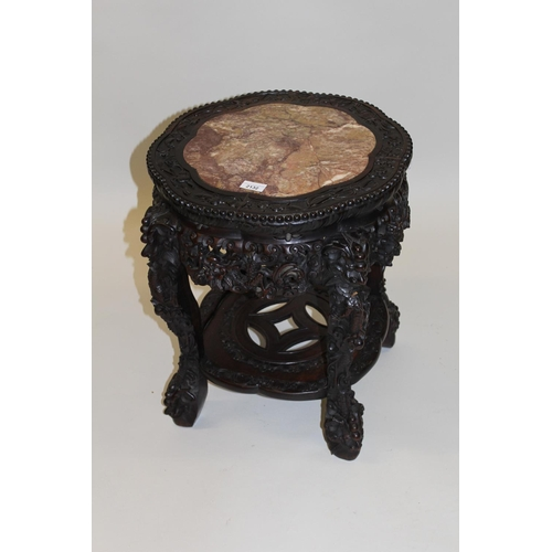 2132 - Chinese circular carved hardwood vase stand, the shaped rouge marble inset top above a heavily carve...