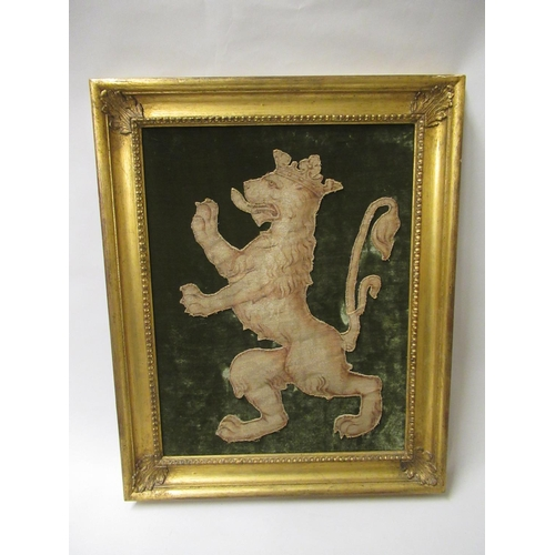 25 - Antique cut-out textile fragment of a lion rampant mounted on a velvet backing, 19ins x 14ins approx...