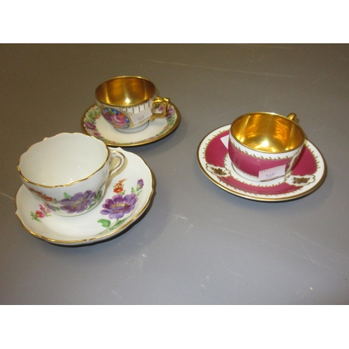 569 - Late Meissen floral decorated cup and saucer and two other cups and saucers with gilt bowls