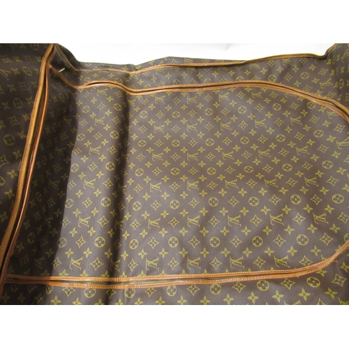 57 - Louis Vuitton, folding suit carrier with leather straps and leather handles (wear from use)...