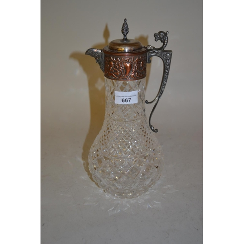 667 - Cut glass claret jug with metal mounts...