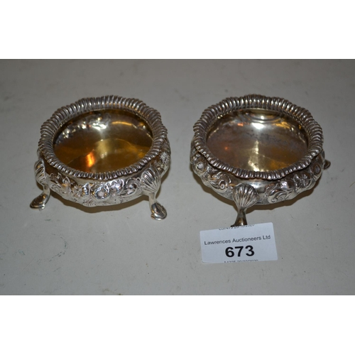 673 - Pair of Victorian silver circular salts with embossed and chased floral decoration on low hoof suppo...