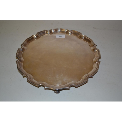 693 - Modern silver circular shaped edge tray on shaped supports, 12.25ins diameter, 28 troy ounces...