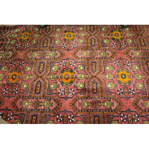 7 - Afghan carpet with three rows of six gols on a wine ground with borders, 11ft x 7ft approximately...
