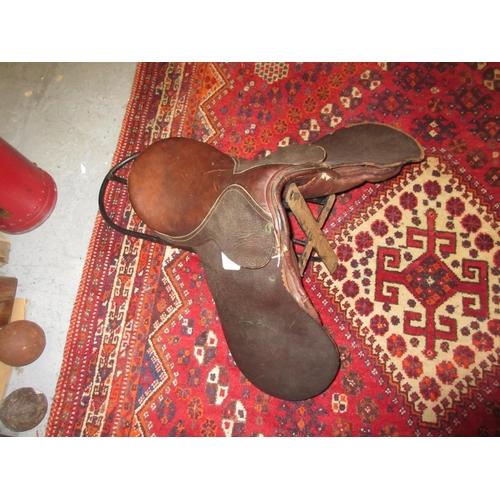 74 - Leather pony saddle and a wrought iron saddle rack...