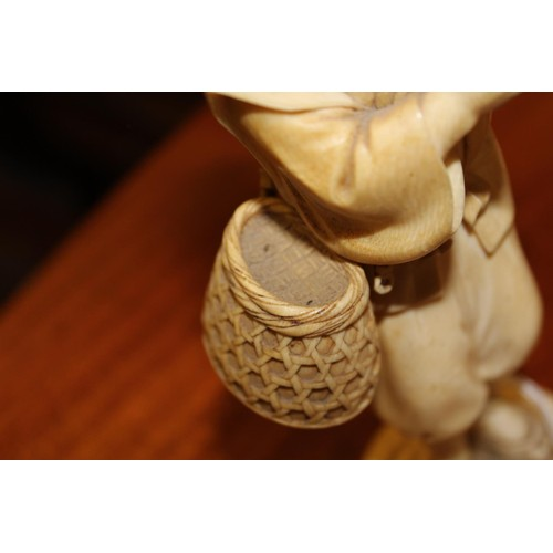 151 - Late 19th Century Japanese ivory okimono in the form of a tradesman standing, carrying a wicker bask...