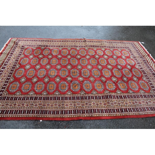 5 - Pakistan Bokhara design carpet having four rows of twelve gols with multiple borders on a wine groun...