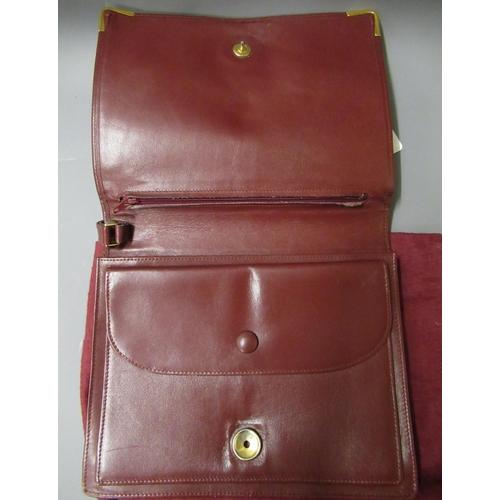 61 - Cartier Pochette bordeaux leather clutch bag, circa 1982, with original dust cover...