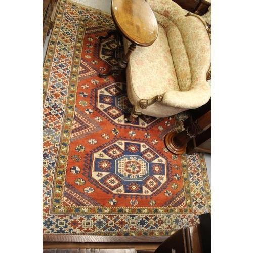 1 - 20th Century Turkish carpet of Kazak design with a triple hooked medallion pattern on a terracotta g...