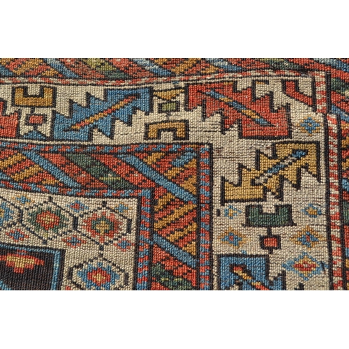 10 - Kazak rug, the centre panel with repeating rosette design on a dark ground with multiple borders, 6f...