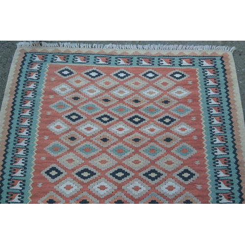 15 - Small Kelim rug with an all-over flower head design on a salmon pink ground with borders, 4ft 8ins x...