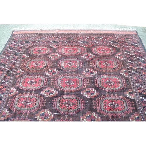 18 - Afghan carpet with three rows of seven gols on a wine ground with multiple borders, 9ft x 7ft 8ins a...