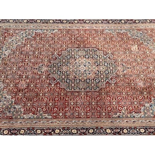 12 - Indo Persian carpet with a medallion and all-over Herati design on a red ground with multiple border...