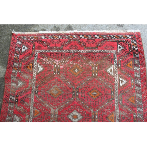 10 - Afghan rug with a repeating hooked medallion design on a wine red ground with borders (some wear), 6...