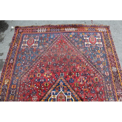 12 - Shiraz rug with a medallion and all over stylised floral design on a red ground, with corner designs...