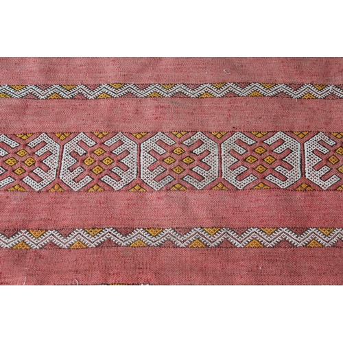 4 - Sumak runner of geometric pattern on a red ground, 99ins x 44ins together with a similar smaller Sum...