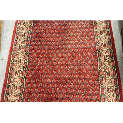 7 - Serabend runner with an all-over Herati design on red ground with borders, approximately 20ft x 2ft ...
