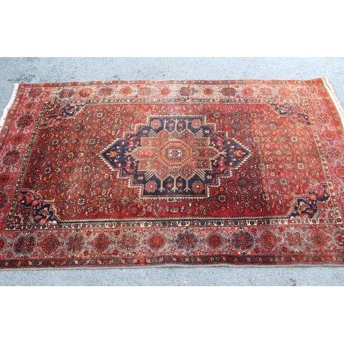 11 - North East Persian rug with a single stepped medallion and all-over Herati design on a red ground wi...