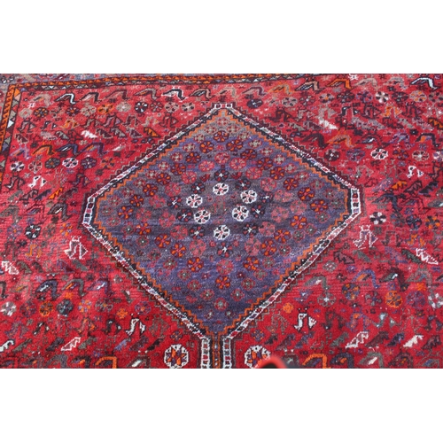 19 - Shiraz carpet with a triple pole medallion and all-over stylised design on a red ground with multipl...