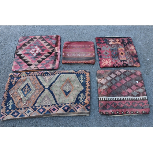 24 - Five Kelim cushion covers and a small flat weave rug