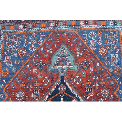28 - Small Qashqai rug with a lobed medallion and all-over stylised design on a red and blue ground with ...