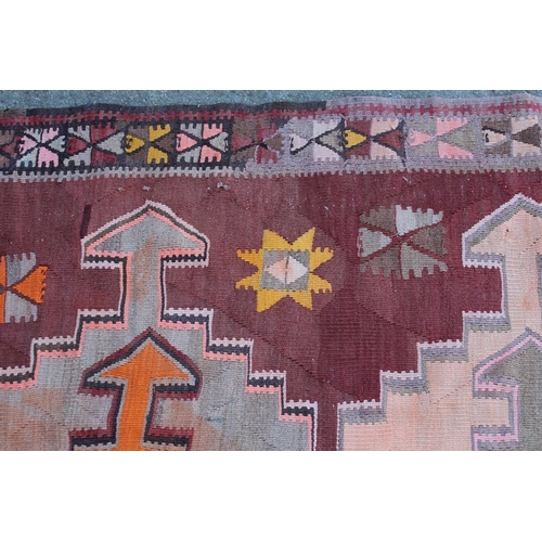 32 - Kelim runner of all-over geometric design on a wine ground, approximately 10ft 6ins x 3ft 6ins