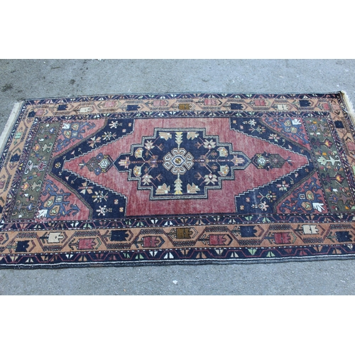 33 - Kurdish rug with centre medallion and all-over floral design on a dark red ground with borders, appr...